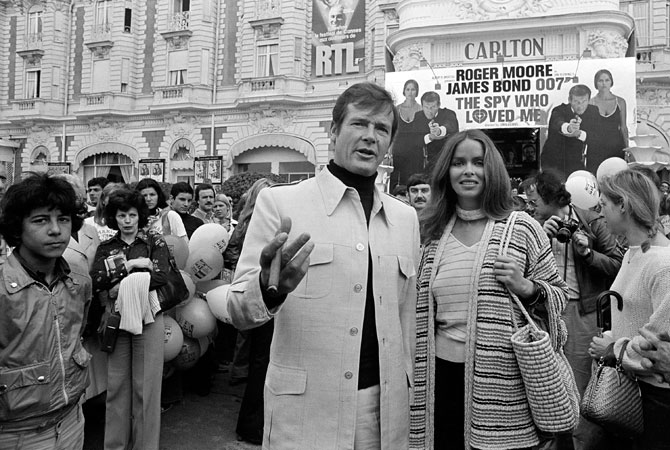 "In this May 20, 1977 file photo, actor Roger Moore, alias British secret agent James Bond, is accompanied by co-star Barbara Bach as they arrive for the screening of their latest 007 feature, ""The Spy Who Loved Me,"" during the Cannes Film Festival at the French Riviera. Moore, played Bond in seven films, more than any other actor."