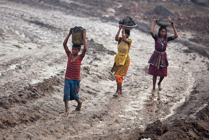Locals carry coal from an open cast coal field at Dhanbad district in the eastern Indian state of Jharkhand.