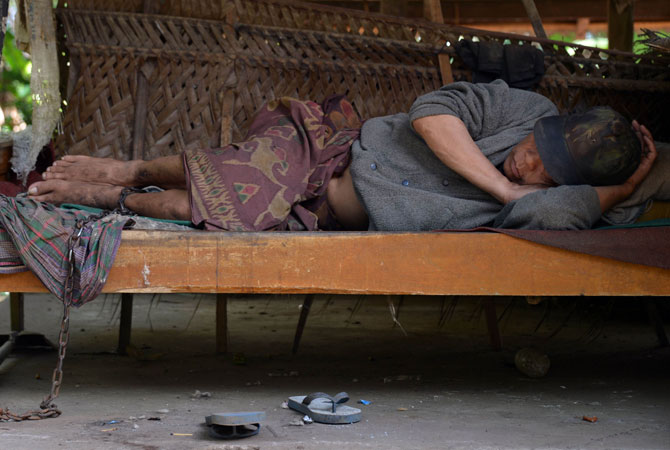 A mental disorder patient, I Ketut Lingga, 54, stays on his bed and chained by his family in Karangasem.  Mental health services lack human and financial resources in many countries, particularly low and middle income countries. More funding is needed to promote mental health to increase people's awareness of the issue.