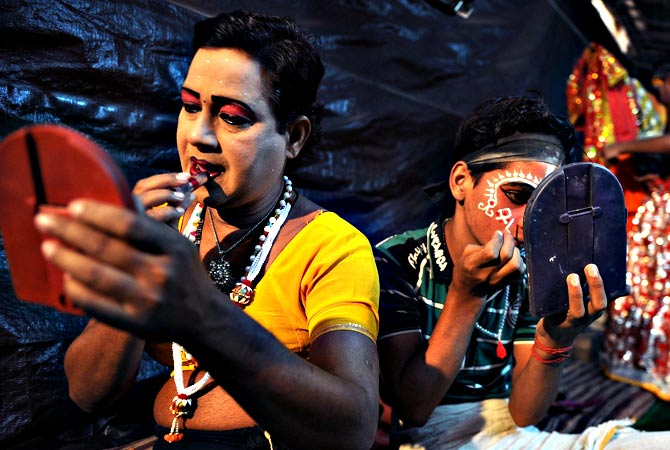 Indian male artist Ram Vilas (L), 42, and junior artist Ajay Kumar, 15, prepare for a show backstage at the Maharashtra Ramlila Manch