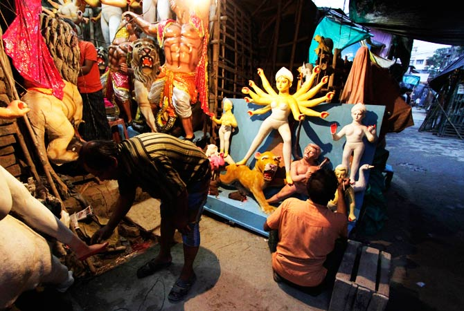 Artisans work on idols of Hindu goddess Durga by the side of a road in Kolkata. ? Photo by AP