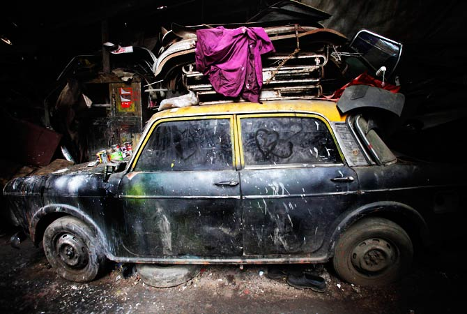 A de-registered Premier Padmini taxi is pictured covered in dust with love hearts etched on its windows at the scrap yard. ? Photo by Reuters