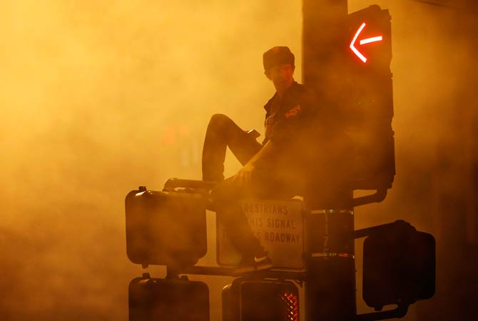 A baseball fan sits on a light post in celebration. ? Photo by Reuters