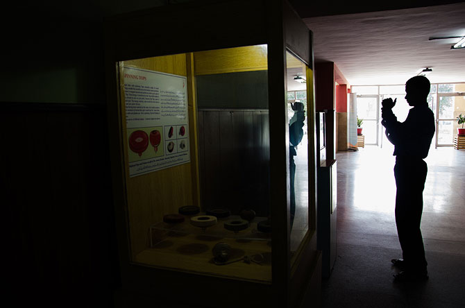A student takes a photo of a display at the entrance of the Mechanics gallery.