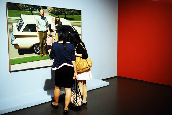 Visitors look at a painting by US artist Robert Bechtle. ? Photo by AFP