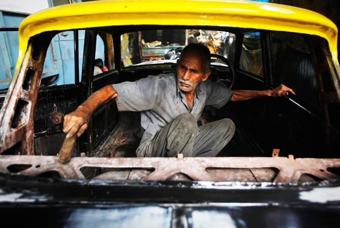A mechanic uses a wire brush to scrub the inside of his taxi before it is refurbished at a workshop. ? Photo by Reuters