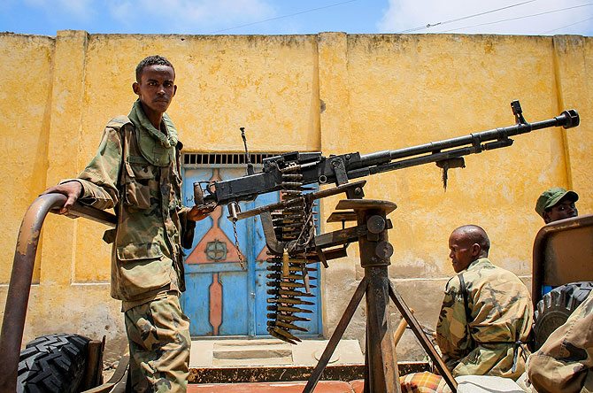 A fighter of the pro-government Ras Kimboni Brigade arms a heavy machine mounted on the back of a pick-up truck while parked along the roadside in the centre of the southern Somali port city of Kismayo.