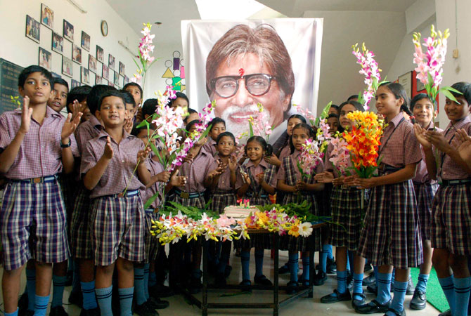 Indian schoolchildren stand in front of a portrait of Bollywood's biggest star Amitabh Bachchan, at an event a day ahead of his 70th birthday, in Mirzapur, India, Wednesday, Oct. 10, 2012.  ? Photo by AP