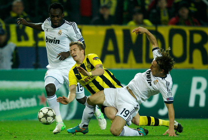 Real Madrid's Michael Essien and Luka Modric challenge Borussia Dortmund's Marco Reus during their Champions League Group D soccer match at BVB stadium in Dortmund. – Photo by Reuters