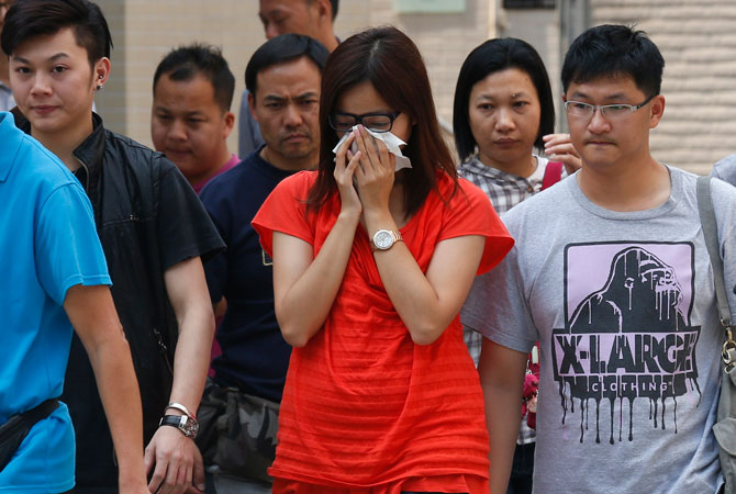 A woman, center, who lost her mother in a ferry collision, leaves a public mortuary with relatives of other victims, in Hong Kong. ? Photo by AP