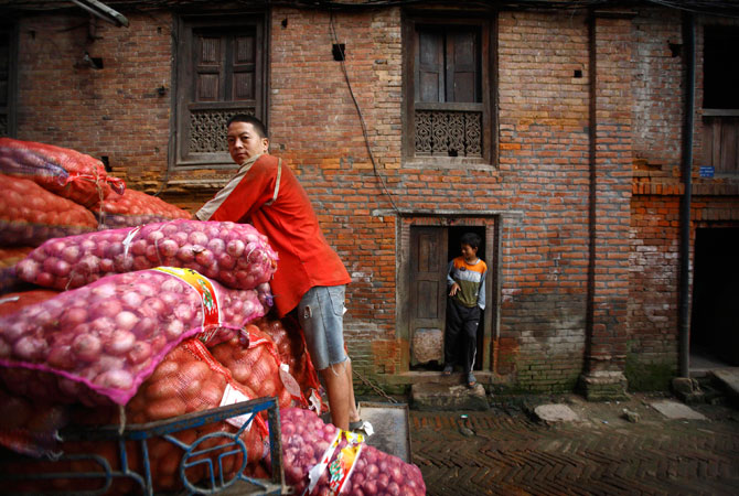 A man stands on the back of a vehicle carrying sacks of onions in the ancient Nepalese city of Bhaktapur.