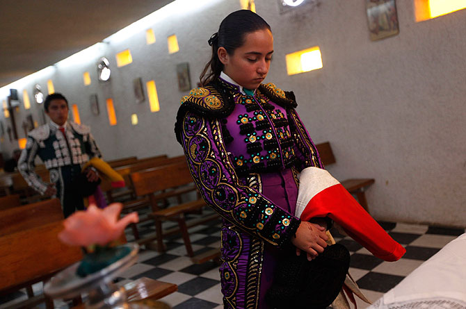 Mexican Novillero (aspiring bullfighter) Paola San Roman, 18, prays before the start of a bullfight at La Mexico bullring in Mexico City September 16, 2012.