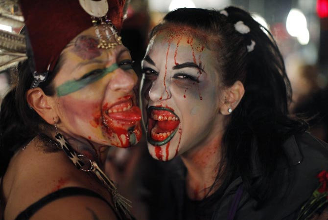 Women dressed up as zombies pose for a picture. - Reuters Photo