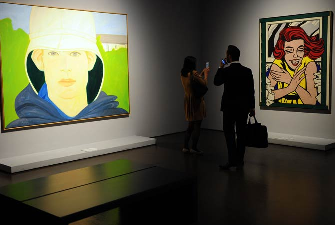 People look at paintings by US artists Alex Katz (L) and Roy Litchtenstein (R)- Photo by AFP