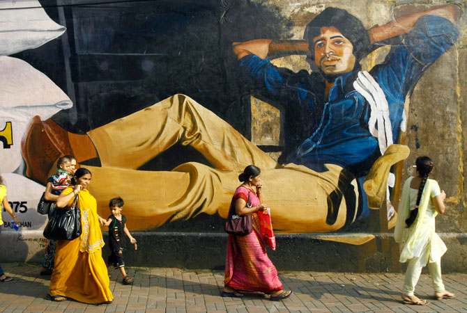 Indians walk past a giant portrait of Bollywood's biggest star Amitabh Bachchan painted on a wall, a day ahead of his 70th birthday, in Mumbai, India, Wednesday, Oct. 10, 2012. ? Photo by AP