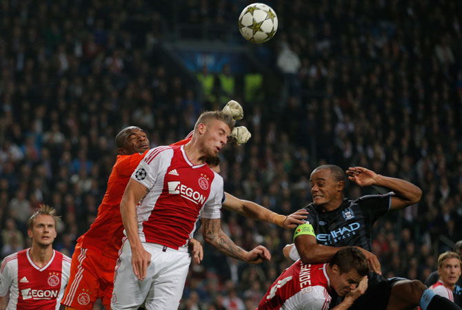 Ajax goalkeeper Kenneth Vermeer, in orange, clears the ball before Manchester City player Vincent Kompany, right, can head the ball Ajax player during the Champions League Group D soccer match at ArenA stadium in Amsterdam, Netherlands. – Photo by AP