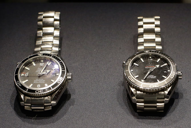 Two Omega watches, left, a Seamaster Planet Ocean model used by Daniel Craig in the James Bond movie 'Quantum of Solace', and a Seamaster Planet Ocean model which is made of Titanium and used by Craig for an action sequence in the upcoming James Bond movie 'Skyfall' is seen during the press preview of the James Bond movie memorabilia charity auction at Christie's auction house in London, Friday, Sept. 28, 2012.  The watches are expected to sell for around 6-8,000 British pounds ($ 9,100-12,00 euro 6,800-9,000) each