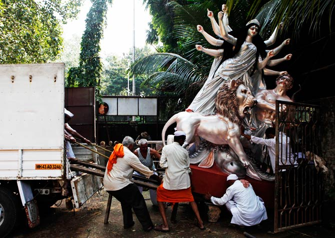 Indians load an idol of Hindu Goddess Durga into a truck to be transported to a place of worship, at a workshop. ? Photo by AP