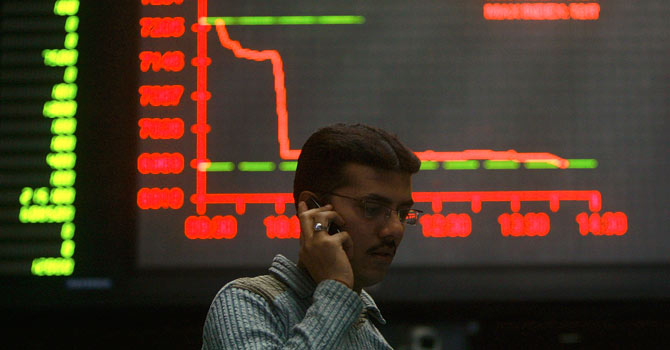 A stockbroker talks on his mobile during a trading session inside the trading hall of the Karachi Stock Exchange – File photo by Reuters