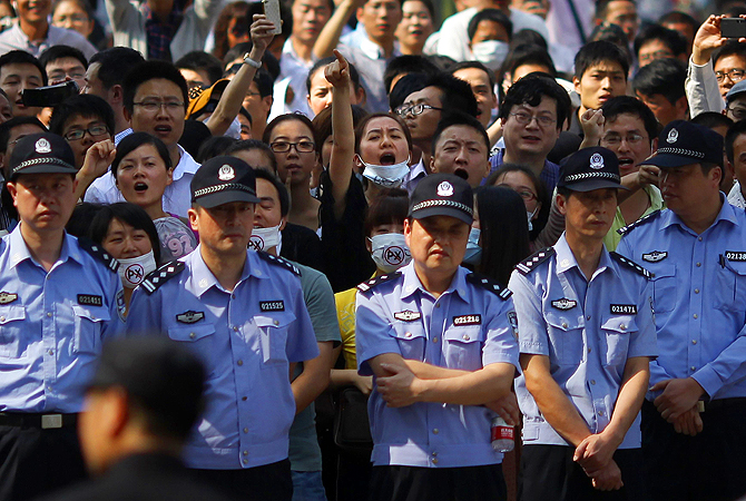 Protesters shout slogans behind a line of police officers during a protest against plans to expand a petrochemical plant in Ningbo. More than a thousand people gathered in the eastern Chinese port city of Ningbo for the protest. Protesters gave out pamphlets denouncing the expansion of the plant by a subsidiary of China Petroleum and Chemical Corporation in the district of Zhenhai.?Photo by Reuters