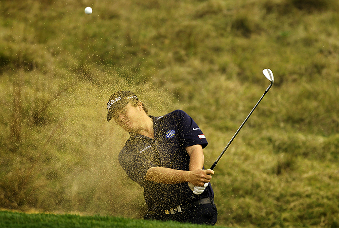 George Coetzee of South Africa hits out of a bunker on the eighth hole during the final round of the BMW Masters 2012 golf tournament at Lake Malaren Golf Club in Shanghai.?Photo by Reuters