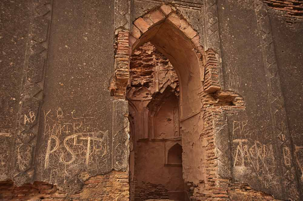 An external view of the Jam Unner tomb. The dynasty that he founded was located in Lar or Lower Sindh, and was first mentioned in 1355 by Ibn-e-Battuta, the famous traveler from North Africa. The facade of the tomb is crumbling and vandalised with scratched political graffiti.  - Photo by Nadir Siddiqi/Dawn.com