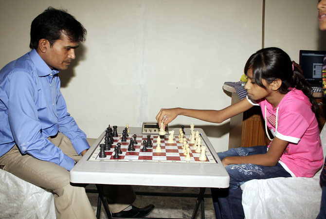 Mahk, age 12 is now the youngest record holder in setting a chessboard in 15 seconds. Guinness Book of World Record team witnessed the event at Expo Center (File photo playing with father). - Photo by INP