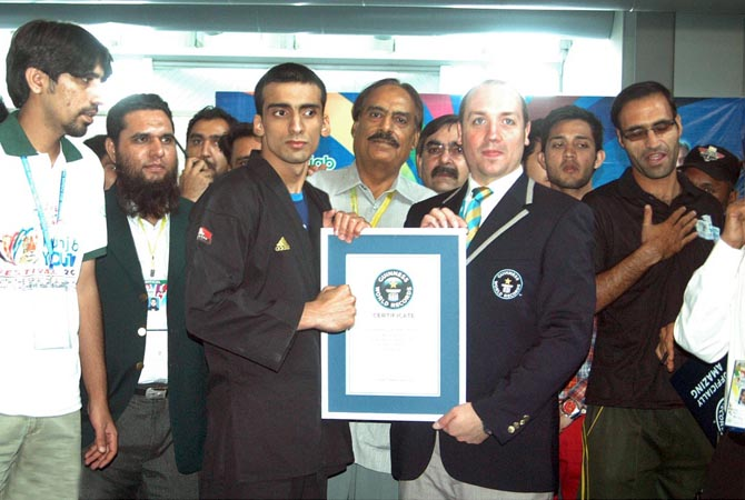 An official giving a certificate of Guinness World Records to Ahmad Bodla who made a world record of 617 kicks in 3 minutes, during the Punjab Youth Festival. - Online Photo