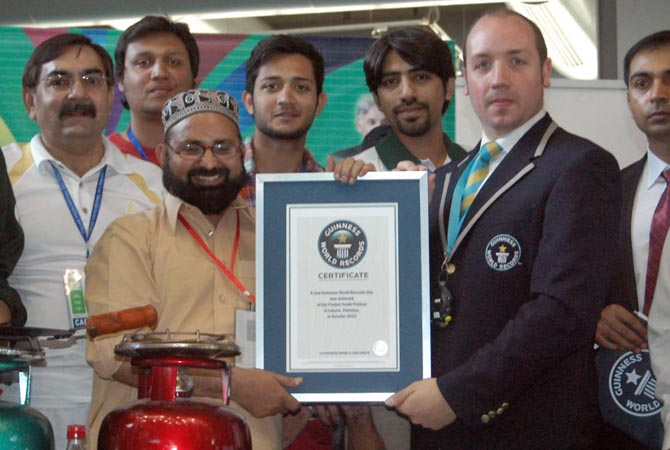 An official giving certificate of Guinness World Records to Muhammad Mansha who made a world record of making 3 breads in 3 minutes and 14 seconds, during the Punjab Youth Festival. - Online Photo