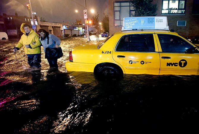 Pedestrians walk past a submerged taxi in Brooklyn, New York.-Photo by Reuters