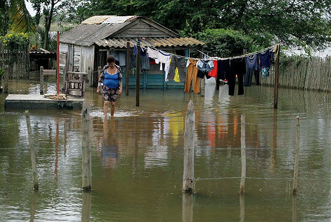 A woman walks in her yard, flooded after Hurricane Sandy, in the village of Hoyo Colorado in central Cuba, around 170 kilometres (100 miles) east of Havana.-Photo by Reuters