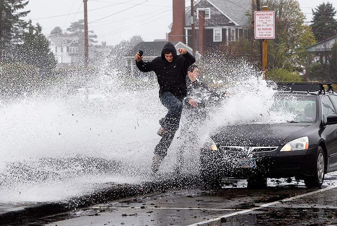 A large wave crashes over a seawall on the Atlantic Ocean during the early stages of Hurricane Sandy.-Photo by AFP