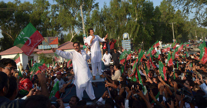 Pakistan cricket star turned politician Imran Khan (C) addresses supporters as he stands on a vehicle during a rally in Mianwali, northern Pakistan, on October 6, 2012. Pakistani cricketer turned politician Imran Khan led Western activists and thousands of supporters on a defiant march to the tribal belt to protest against US drone strikes. Crowds lined the road to greet Khan, and scrums of media and well-wishers thronged his 4X4 as the convoy of more than 100 vehicles embarked on the 440-kilometre (270-mile) drive from Islamabad to South Waziristan. AFP PHOTO