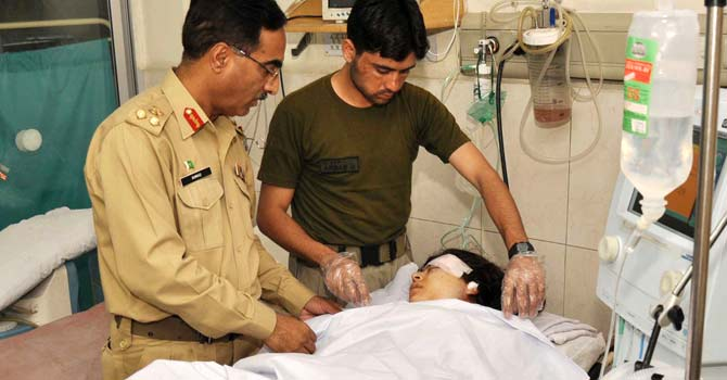 In this handout photograph released by the Pakistan's Inter Services Public Relations (ISPR) office on October 9, 2012, Pakistani army doctors give treatment to injured Malala Yousafzai, 14, at an army hospital following an attack by gunmen – Photo by AFP