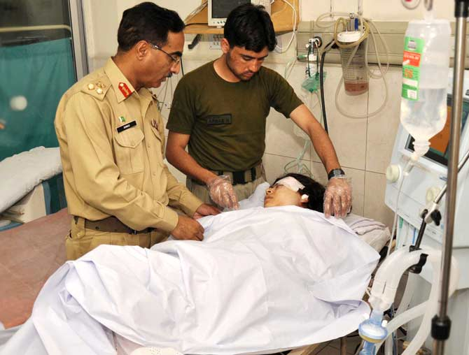 In this handout photograph released by the Pakistan's Inter Services Public Relations (ISPR) office on October 9, 2012, Pakistani army doctors give treatment to injured Malala Yousafzai. - Photo by AFP