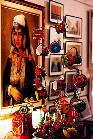 Handpainted vibrant tin cups with a painting in the background — Photo by Eefa Khalid/Dawn.com