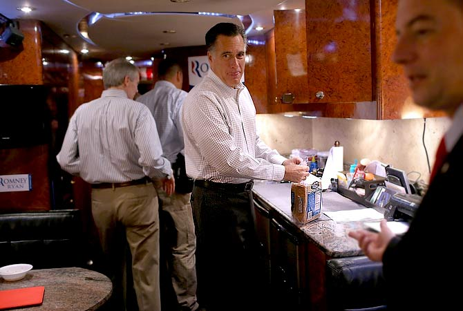 Republican presidential candidate, former Massachusetts Gov. Mitt Romney (C) prepares to make a peanut butter and honey sandwich as Republican National Committee chairman Reince Priebus (R) looks on aboard his campaign bus en route to a campaign rally at Avon Lake High School in Avon Lake, Ohio. Romney canceled campaign events on October 29 and 30 due to Hurricane Sandy.-Photo by AFP
