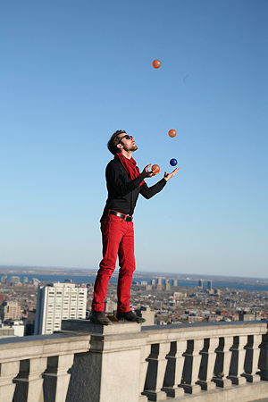Mount Royal attracts a lot of visitors and the inevitable performers.  Here a young man is juggling balls - and yes, there is a sheer drop right behind him!  St Lawrence River and the South side of the city can be seen behind him.