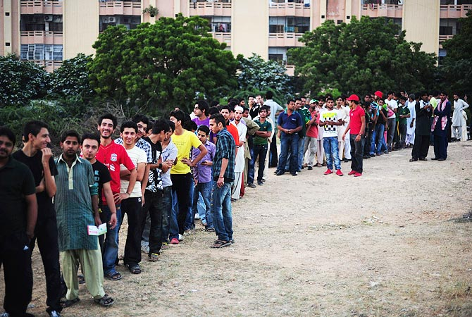 Pakistani cricket fans queue outside the National Stadium prior to the start of the Twenty 20 match between International World XI and Pakistan All Stars. -Photo by AFP