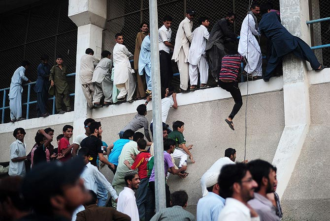 Fans climb the walls of the National Stadium, Karachi prior to the start of the match. -Photo by AFP