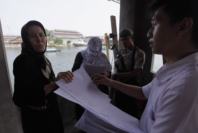 Officers (R) give immigration forms to ethnic Hazara women who were detained by Indonesian police at Pondok Dayung in Jakarta, October 25, 2012.