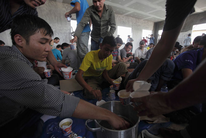 Ethnic Hazaras cook noodles as they are detained by the Indonesian police at Pondok Dayung in Jakarta, October 25, 2012.