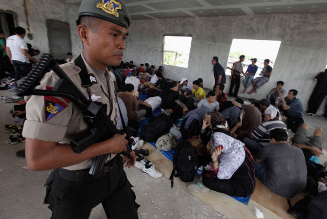 An Indonesian policeman walks by detained ethnic Hazaras in Pondok Dayung in Jakarta, October 25, 2012.