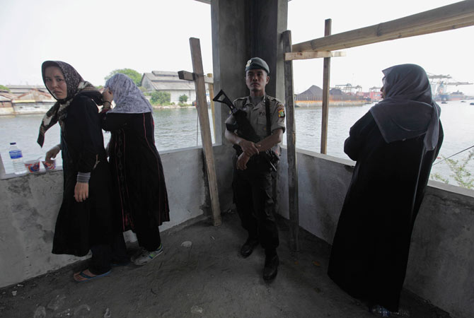 Detained ethnic Hazara women stand by an Indonesian policeman at Pondok Dayung in Jakarta, October 25, 2012.