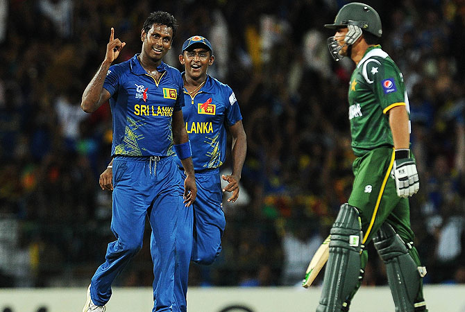 Angelo Mathews (L) celebrates with teammate Ajantha Mendis (C) after he dismissed Pakistan batsman Kamran Akmal. -Photo by AFP