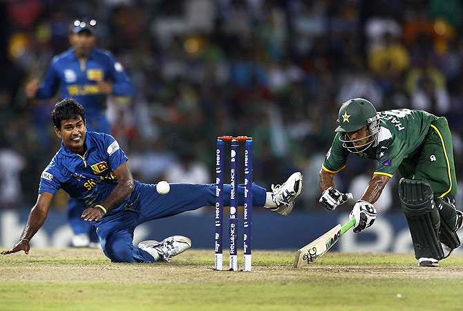Sri Lanka's bowler Nuwan Kulasekara, left, attempts to run-out Pakistan's captain Mohammad Hafeez. -Photo by AP