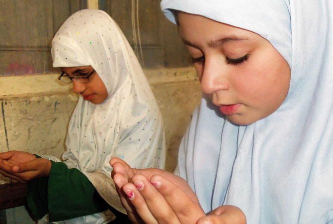 Pakistani students pray for the early recovery of Malala Yousafzai.