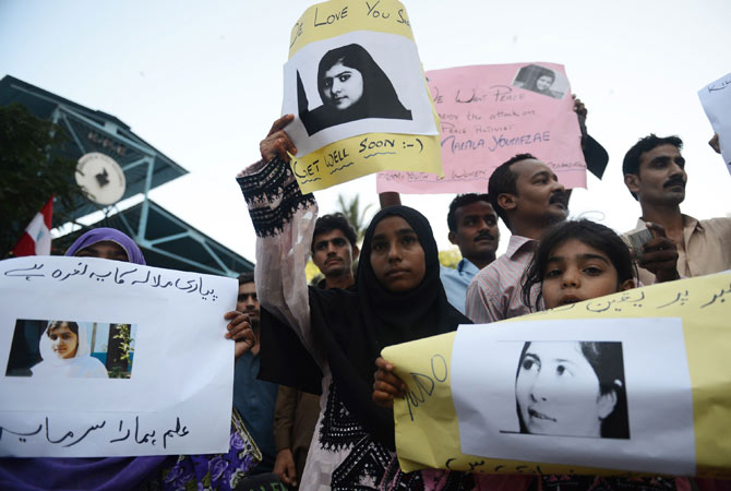 Pakistani demonstrators carry photographs of gunshot victim and child activist Malala Yousafzai during a protest against her assassination attempt.
