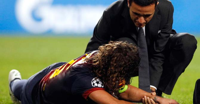 Barcelona's Carles Puyol (L) receives assistance after falling and sustaining an injury during their Champions League Group G soccer match against Benfica at the Luz stadium in Lisbon – Photo by Reuters