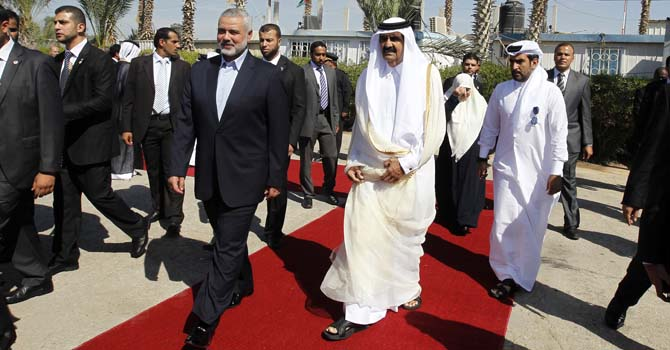 Qatari Emir  Sheikh Hamad bin Khalifa al-Thani (C-R) walks alongside Gaza's Hamas prime minister Ismail Haniyeh (C-L) during a welcome ceremony at the Rafah border crossing with Egypt  on October 23, 2012 in the Gaza Strip. Sheikh Hamad bin Khalifa al-Thani arrived in the Gaza Strip in the first visit by a head of state since the Islamist Hamas movement took over in 2007. AFP PHOTO/MOHAMMED ABED